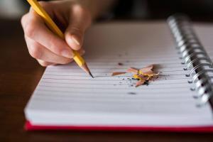 Government issues new asbestos guidance for schools - pupil writes with pencil